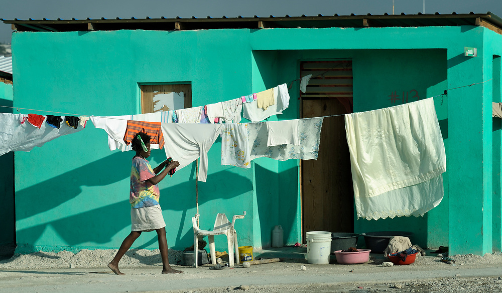 A woman hangs up her laundry to dry in Cite Soleil, a sprawling poor portion of Port-au-Prince, Haiti. She lives in one of several new homes for earthquake survivors constructed by an Italian nun working in the neighborhood.