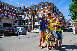 Outnumbered but hoping for victory, A Colombian family and their dog Troy are pictured on the Kirby Estate in Southwark where local residents have put on a huge display of support for England in the World Cup. PICTURED: Daughter Alejandra Ramos, 29 (mother of Adeline), Mother Sandra Ramos, 48, her Grand-daughter Adeline, seven months, and her Son Jean-Paul Jhonnes, 19 with Troy their American Boxer Dog . London, July 02 2018.