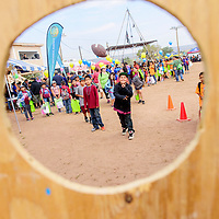 Toby Williams of Ganado Elementary rockets a pass through a hole to win a new football during Ashkii Happy Kids Day at the Navajo Nation fairgrounds in Window Rock Thursday.