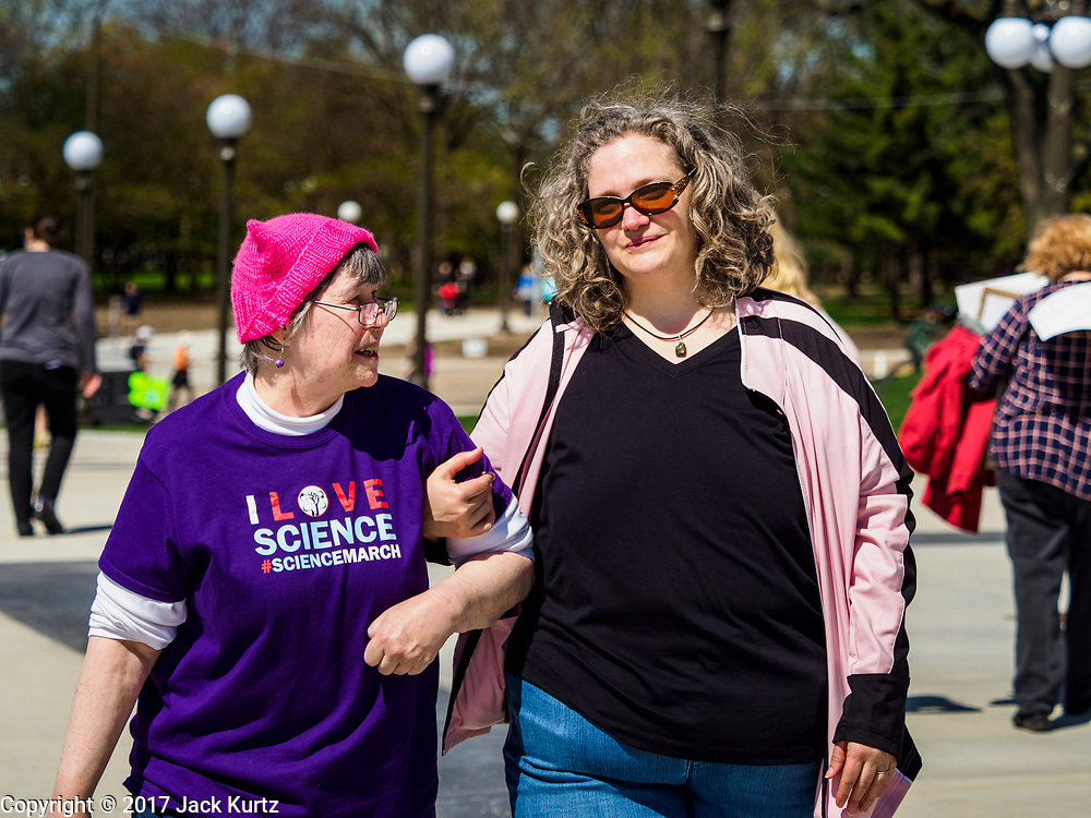 """22 APRIL 2017 - ST. PAUL, MN: A woman wearing the """"pink pussy hat"""" from the women's march in January arrives at the March for Science at the Minnesota State Capitol. More than 10,000 people marched from the St. Paul Cathedral to the Minnesota State Capitol in St. Paul during the March for Science. March organizers said the march was non-partisan and was to show support for the sciences, including the sciences behind climate change and vaccines.      PHOTO BY JACK KURTZ"""