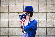 Aubrey Meade of Lincoln Park, Michigan wipes her face with an American flag before stilt walking in the annual Independence Day Parade in Oak Park, Michigan on Wednesday, July 4, 2018.<br /> <br /> Credit: Cameron Pollack / Detroit Free Press