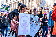San Francisco, USA. 19th January, 2019. Two young girls march together, smiling and holding signs at the Women's March San Francisco. Credit: Shelly Rivoli/Alamy Live News
