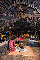 Dassanach tribe woman using a grindstone inside her hut, Omo Valley, Ethiopia.