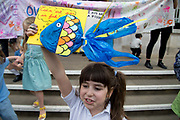 London Borough of Hackney, London. May 24th . Third strike by school students but Hackney primary school pupils went to the Town Hall after school to protest about the climate emergency. Blanche holds a placard with a blue plastic bag in the shape of a fish and the words I am not a fish , referencing Magritte.