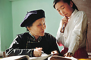 A teacher helps a student in the classroom of Batbilig Batsuuri in Ulaanbaatar, Mongolia. From coverage of revisit to Material World Project family in Mongolia, 2001.