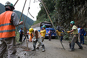 Road workers testing the bedrock density while truck drivers watch for the road to be reopened on the Interoceanic  Highway near San Gaban