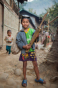 A boy poses proudly with his diving mask, spear gun, and homemade string instrument in Ban Huay Phouk, Laos.