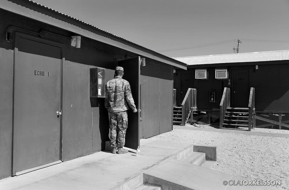 """A military guard at the prison camp at Guantanamo, Cuba, Jan 28 2017, guards a door to a room where the prisoners can meet and talk with their lawyers.<br /> The guards turn away their faces so you cannot identify them. It is standard operation procedure when pictures are made. When you work as a journalist at the Guantanamo you work under military censorship and all your material is checked every day and approved for publication.<br /> The prison camp on the Guantánamo naval base was the creation of President George W. Bush. The prison camp was considered an important part of the US war on terrorism. Over the years, 779 people have been brought to the camp. 41 people are still detained. Of them, 26 people count as """"forever prisoners"""", indefinite detainees under the Law of War. Two prisoners have been in the camp since it was opened in January 2002. The last prisoner taken to the camp came in March 2008. The so-called war on Terror and the Guantanamo prison camp have been heavily criticized for violation of human rights regarding torture and habeas corpus.<br /> It is unclear what US President Donald Trump wants to do with the camp, but during the election campaign he said that he would fill Guantánamo Bay with """"bad dudes"""". Photo by Ola Torkelsson<br /> Copyright Ola Torkelsson ©"""
