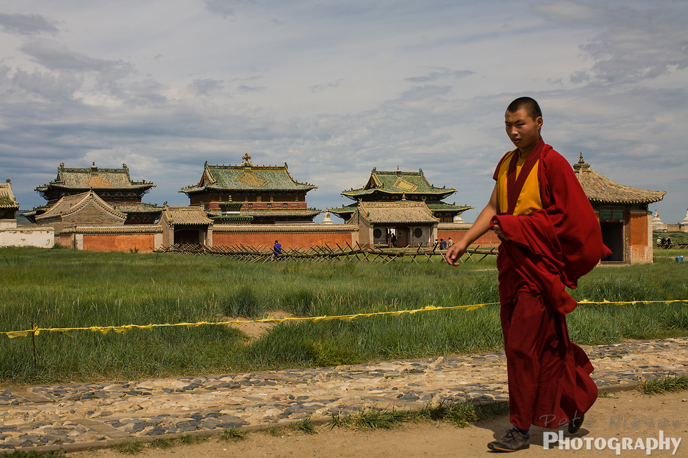 Mongolian Buddhist monk walking thrpough ancient temple grounds