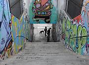 Tourists peruse street art lining a walkway in Cerro Alegre, Valparaiso.