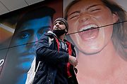 A man wearing a face covering on his chin and with a cigarette in his mouth, walks beneath a large billboard featuring an ecstatic young woman, on the exterior of a soon-to-open fitness club opposite Liverpool Station in the City of London, the capitals financial district, on 24th February 2021, in London, England.