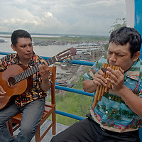 Peruvian folk musicians sing in a restaurant overlooking the busy Amazon River harbor in Iquitos, Peru.