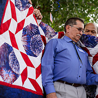 Army veteran Chuck Padilla is draped in a quilt during the Quilts of Valor ceremony at the University of New Mexico-Gallup North Campus in Gallup Friday.