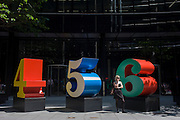 A city worker uses her smartphone by an art installation entitled 'One Through Zero (The Ten Numbers)' by American pop artist Robert Indiana (b 1928), in Lime Street, City of London, the capital's Square Mile, and its financial heart. Situated in the capital's Square Mile, its financial heart, are surrounding offices and corporate headquarters from the finance and insurance sector, most notably being the nearby Lloyds of London building. This series of sculptures is composed of 10 brightly painted numerical digits, each made of aluminum and set on its own base. Their construction took place at the former Lippincott Foundry in North Haven, Connecticut from 1980 to 1983
