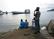 MWANZA, TANZANIA.  Men watch as a ferry steams to port on the shore of Lake Victoria in Mwanza, Tanzania on Thursday, September 4, 2014.  © Chet Gordon/THE IMAGE WORKS