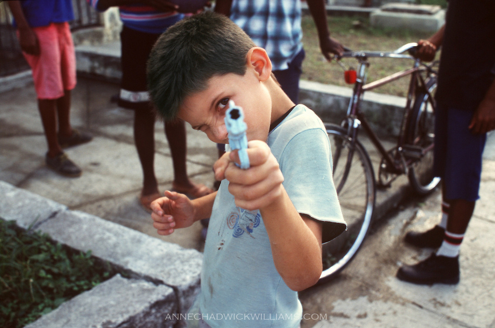 A boy in Havana, Cuba plays with a toy gun.