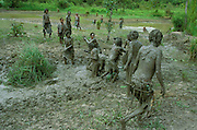 Dani women engaging in a ritual mud battle during a girl's hotaly, her first menstruation ceremony, in the Baliem Valley, Papua Region, Indonesia. The mud battle takes place after a night of singing and dancing in the cooking house of the settlement where the girl lives.