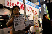A supporter hands out information for Former Japanese Air Self Defense Force (JASDF) Chief of Staff, Toshio Tamogami, as he campaigns for election as Tokyo Governor. Shibuya, Tokyo, Japan. Friday, January 17th 2014. Tamogami was forced to resign his position as a general in the JASDF when he wrote a essay questioning the accepted history of Japan's aggression in the 1930s and 40s. He leads the right-wing pressure and political group, Ganbare Nippon and is supported in his gubernatorial bid by nationalist former governor, Shintaro Ishihara.