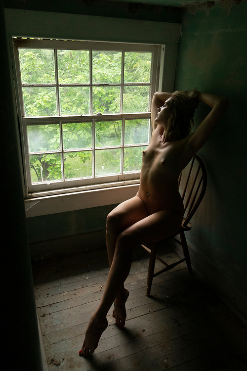 Photo of a sexy, nude woman sitting at a window in an attic