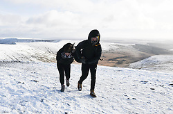 © Licensed to London News Pictures. 04/12/2020. <br /> Two people brace against the wind on Penyfan, in the Brecon Beacons, the highest point in southern Wales and England, which has seen it's first snowfall of the year. Photo credit: Robert Melen/LNP