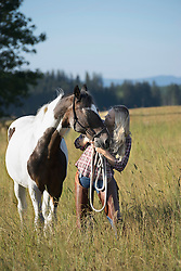 Mid adult woman standing with her horse on meadow, Bavaria, Germany