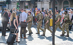 © Licensed to London News Pictures. 25/05/2017. London, UK. Armed soldiers and police walk past commuters at Victoria Station in Westminster, London following a terrorist attack in Manchester, northern England, earlier this week. 23 people were killed an dozens more injured when Salman Abedi set off a suicide bomb at an Ariana Grande concert.  Photo credit: Ben Cawthra/LNP