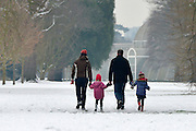 © Licensed to London News Pictures. 19/01/2013. Kew, UK A family walk toward the glasshouse. People enjoy the snow at Kew Gardens in West London today 19th January 2013. More cold weather and snow are expected over the coming days.  Photo credit : Stephen Simpson/LNP