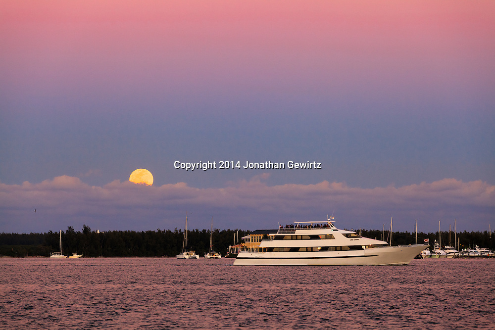 A motor yacht with a deck full of passengers cruises through Miami harbor towards southern Biscayne Bay and the Atlantic Ocean, as the full moon rises over Virginia Key in the background.<br /> WATERMARKS WILL NOT APPEAR ON PRINTS OR LICENSED IMAGES.