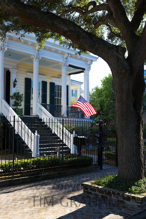 Traditional clapboard grand house with columns, stars and stripes flag in the Garden District of New Orleans, Louisiana, USA