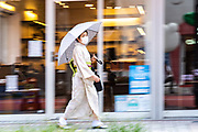 A Japanese woman dressed in a traditional kimono walks down a street in the historic Asakusa neighborhood in Tokyo, Japan.
