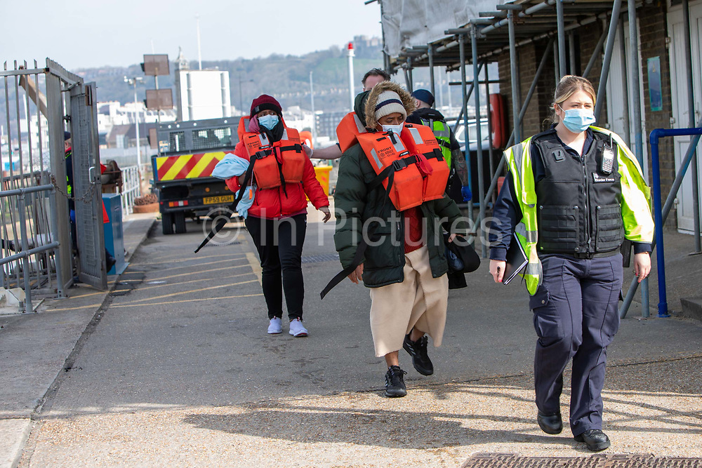 Asylum seekers arriving into Dover accompanied by Boarder Force officers after being on board a Boarder Force RIB boat, they were rescued in the English Channel while crossing in small inflatable dinghy on the 31st of March 2021 in Dover, Kent, United Kingdom. About 30 men and women arrived today on two small boats they were taken off the boat by UK Boarder Force and taken into a processing centre on the dock side.