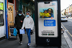 "© Licensed to London News Pictures. 26/09/2020. London, UK. A couple wearing face masks walk past 'Protect your loved ones. Get the App' digital advert in north London, which is a part of the government's new public information campaign on NHS COVID-19 Track And Trace App. The app was launched early this week after months of delay and questions about its effectiveness. Health Secretary MATT HANCOCK said that, ""Every single person who downloads the app is helping to improve how it can keep us safe. It helps you to keep yourself and your loved ones safe."" Users who have tested negative for COVID-19 are unable to input and share the results on the NHS app, if they did not book the test via the app in the first place. Photo credit: Dinendra Haria/LNP"