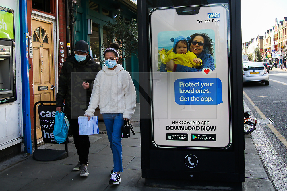 """© Licensed to London News Pictures. 26/09/2020. London, UK. A couple wearing face masks walk past 'Protect your loved ones. Get the App' digital advert in north London, which is a part of the government's new public information campaign on NHS COVID-19 Track And Trace App. The app was launched early this week after months of delay and questions about its effectiveness. Health Secretary MATT HANCOCK said that, """"Every single person who downloads the app is helping to improve how it can keep us safe. It helps you to keep yourself and your loved ones safe."""" Users who have tested negative for COVID-19 are unable to input and share the results on the NHS app, if they did not book the test via the app in the first place. Photo credit: Dinendra Haria/LNP"""
