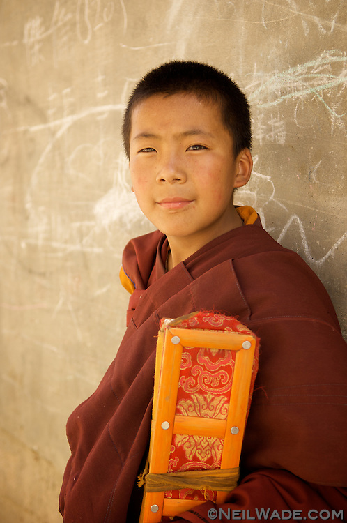 A novice Tibetan monk holding holy scriptures from the famous printing press in Dege, China (Tibet).