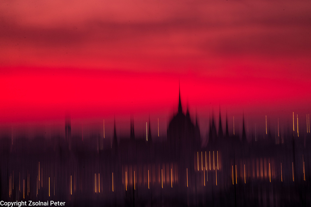 The sun is rising behind the Houses of Parlament of Budapest, Hungary viewed from the Mansfeld Peter park.