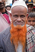 An orange bearded man stands at the Sonargaon market in the town of Sonargaon outside Dhaka, Bangladesh.