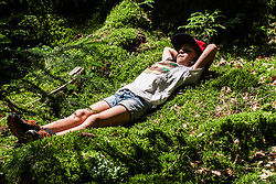 Girl lying on moss in forest
