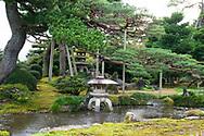 A stone lantern in a stream under a pine tree in the Kenrokuen Garden, Kanazawa, Japan