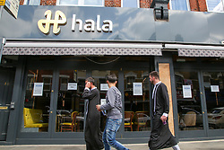 "© Licensed to London News Pictures. 24/05/2020. London, UK. Muslim men walk past ''HALA' a Turkish restaurant on Green Lanes, Haringey in north London which is open for take away only due to coronavirus lockdown, as Muslims celebrate Eid al-Fitr. On Eid al-Fitr also known as ""Festival of Breaking the Fast"", a religious holiday celebrated by Muslims worldwide that marks the end of the month-long fasting of Ramadan, restaurants would normally be packed with people celebrating Eid. Photo credit: Dinendra Haria/LNP"