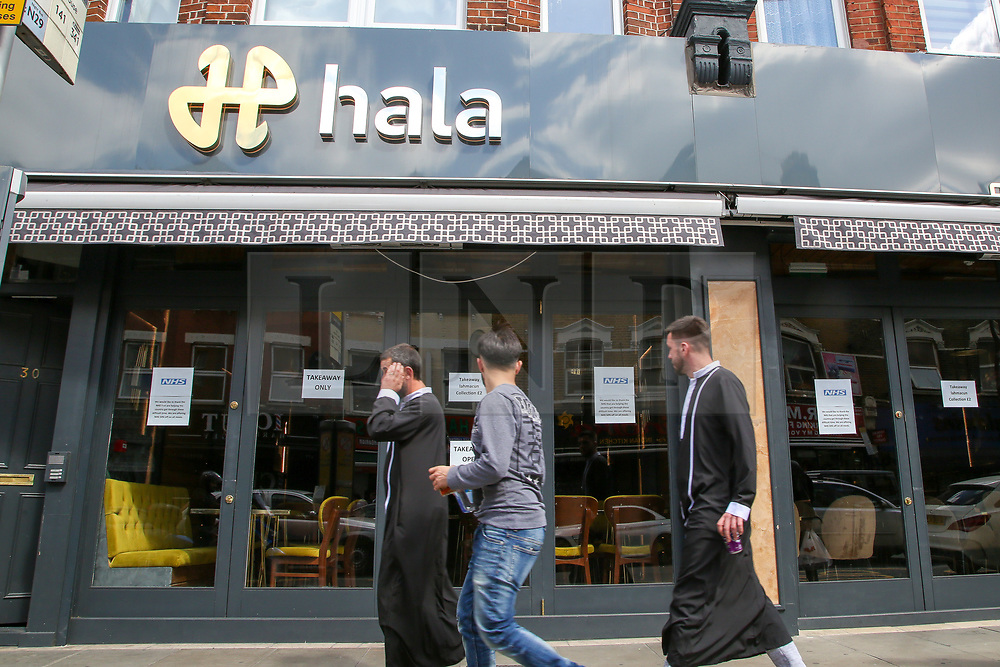 """© Licensed to London News Pictures. 24/05/2020. London, UK. Muslim men walk past ''HALA' a Turkish restaurant on Green Lanes, Haringey in north London which is open for take away only due to coronavirus lockdown, as Muslims celebrate Eid al-Fitr. On Eid al-Fitr also known as """"Festival of Breaking the Fast"""", a religious holiday celebrated by Muslims worldwide that marks the end of the month-long fasting of Ramadan, restaurants would normally be packed with people celebrating Eid. Photo credit: Dinendra Haria/LNP"""
