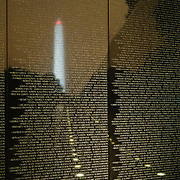 Night shot of the Vietnam Veterans Memorial with the Washington Monument reflected off the names of those killed in Vietnam.
