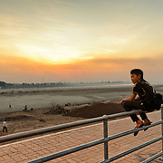Three boys sit on the railing of a walkway along the banks of the Mekong River in downtown Vientiane, Laos, as the sun sets in the distance. The far bank, across the river, is Thailand.
