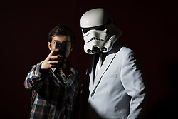 © Licensed to London News Pictures . 16/12/2015 . Manchester , UK . A man takes a selfie with a smartly dressed Storm Trooper in the cinema . Star Wars fans attend the midnight screening of Star Wars the Force Awakens at the AMC Great Northern cinema in Manchester City Centre . Photo credit : Joel Goodman/LNP