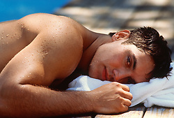 Portrait of a wet young man lying on a white towel beside a swimming pool