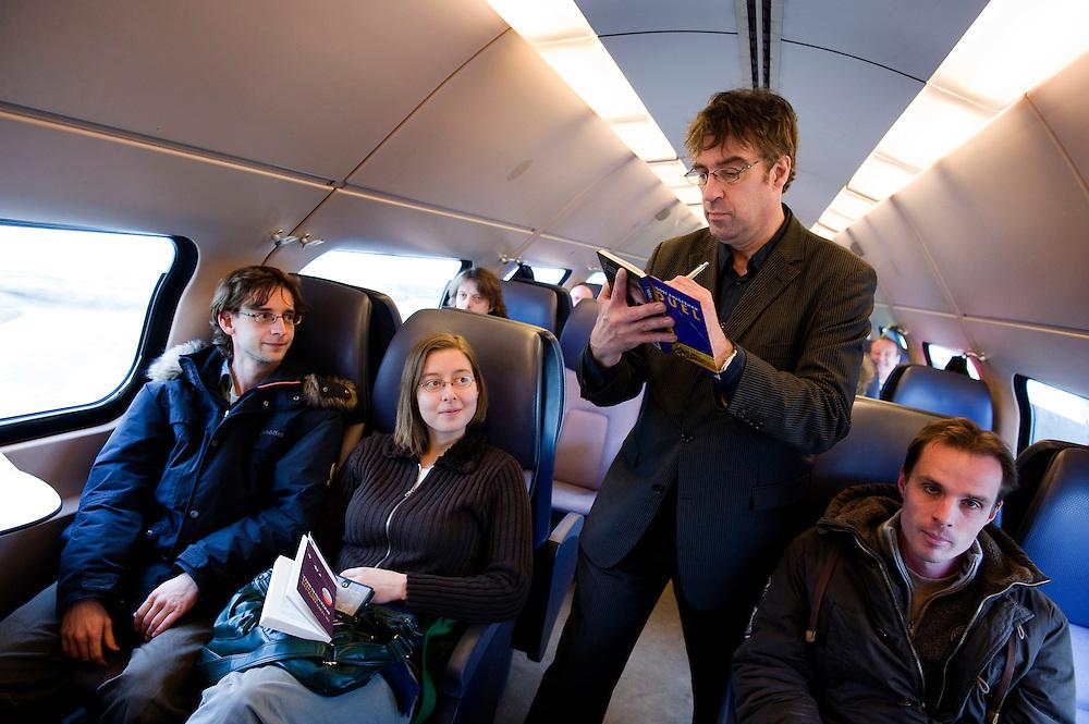 Nederland, Utrecht, 14 maart 2010.Joost Zwagerman, auteur van het boekenweekgeschenk, kontroleert vervoersbewijzen in de trein. Vandaag geldt het boekenweekgeschenk als treinkaartje. Zwagerman signeert alle boeken, de conducteur zet vervolgens zijn knipje in het boek...Foto Michiel Wijnbergh