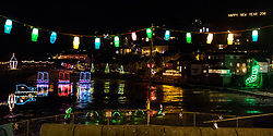 © Licensed to London News Pictures. 27/12/2017. Penzance, UK. The Mousehole Christmas lights illuminate the harbour in Mousehole, Cornwall. The annual light display represents the lanterns that guided fishermen home during rough seas over the Christmas period, in the traditional tale of the 'Mousehole Cat'. Photo credit : Tom Nicholson/LNP