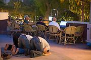 Three men take time to pray at the Gezira Club in Zamelek, Cairo, Egypt