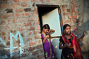 Poonam, 11, (left) and her sister Jyoti, 12, (right) are having an afternoon break before leaving to attend afternoon tuition lessons close to their newly built home in Oriya Basti, one of the water-contaminated colonies in Bhopal, central India, near the abandoned Union Carbide (now DOW Chemical) industrial complex, site of the infamous '1984 Gas Disaster'.