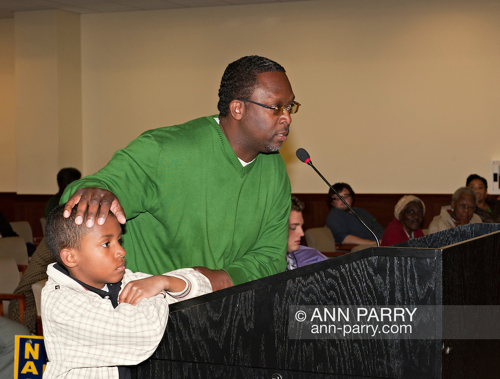 MAY 9, 2011 - MINEOLA, NY: Ramel Smith speaking at podium, with hand on young son's head, at Nassau County Public Hearing on Legislative Redistricting