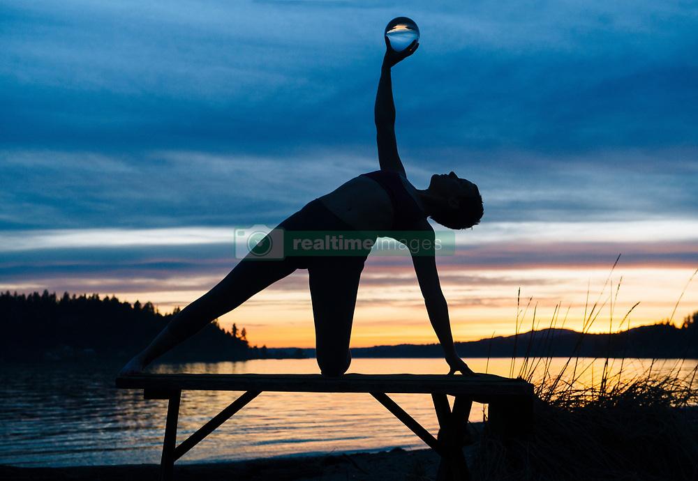 February 9, 2016 - Woman practising yoga by lake at sunset (Credit Image: © Image Source via ZUMA Press)